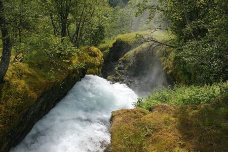 rapid flow of the river among the green forest, rocky shores