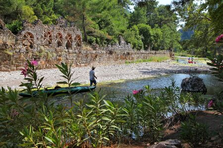 a man with a boat on the river is among the ruins and green plants