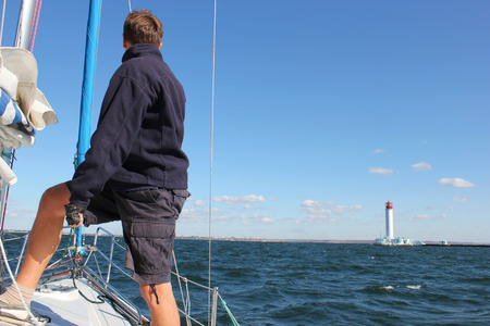man on the bow of the yacht in the sea looking at the lighthouse