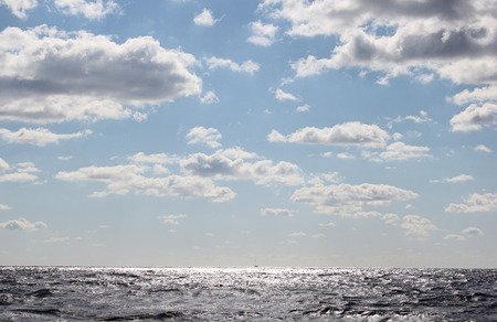 seascape rough sea and blue sky with fluffy clouds