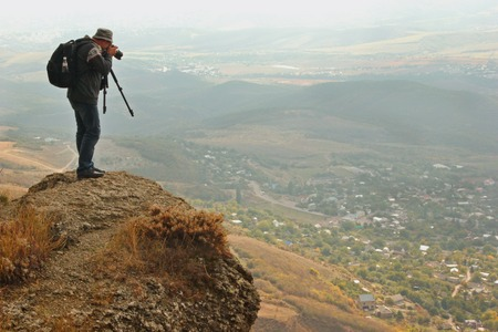 man on the edge of a cliff photographing the landscape of the valley