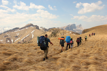 hiking group of tourists cross the ridge trail through a field of yellow grass