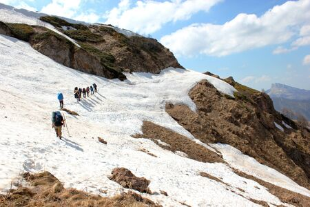 hiking group of tourists cross the ridge trail through the snow slope Stock Photo