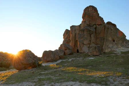 sun rays of the setting sun illuminating the rock