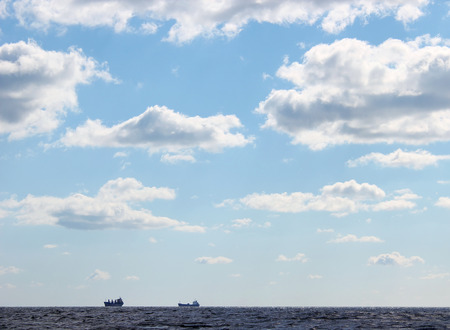 seascape blue sky and silhouettes of two ships on the horizon Stock Photo