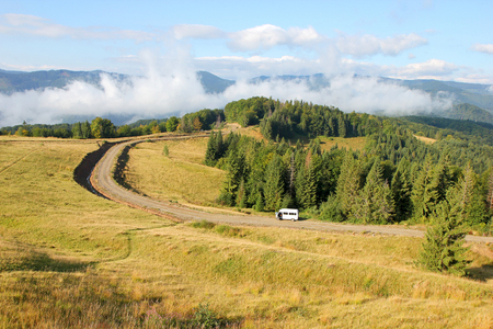 rural road along the edge of the forest in the valley of the highlands photo