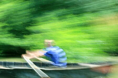 speed blur man rowing a boat green background Stock Photo