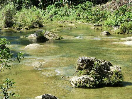 the river runs through the stones down the jungle Stock Photo