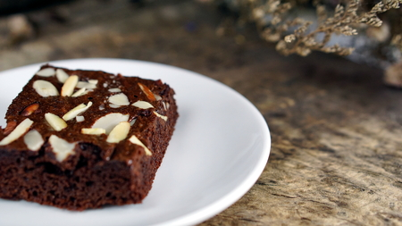 Chocolate brownie put on a wood table with dark roasted coffee beans Stock Photo