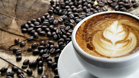 A cup of latte, cappuccino or espresso coffee with milk put on a wood table with dark roasted coffee beans Stock Photo