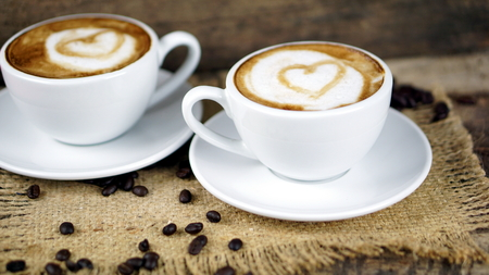 Love cappuccino coffee with hearts. A cup of latte, cappuccino or espresso coffee with milk put on a wood table with dark roasting coffee beans. Drawing the foam milk on top.