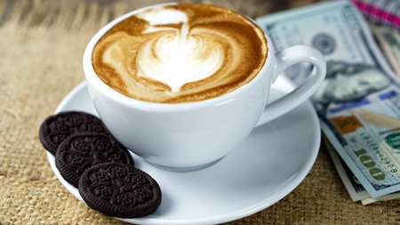 Cappuccino coffee and US Dollars bills. A cup of latte, cappuccino or espresso coffee with milk put on a wood table with dark roasting coffee beans. Drawing the foam milk on top.