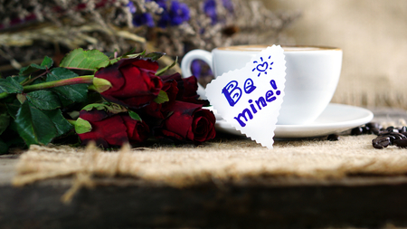 Love cappuccino coffee and roses. A cup of latte, cappuccino or espresso coffee with milk put on a wood table with dark roasting coffee beans. Drawing the foam milk on top. Stock Photo
