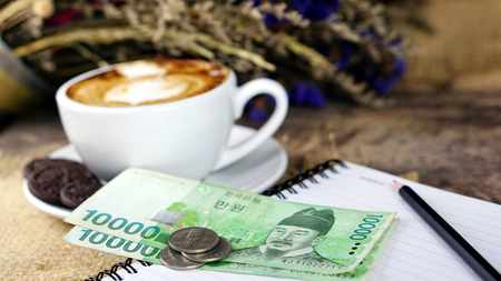 Cappuccino coffee and Won Korea bills. A cup of latte, cappuccino or espresso coffee with milk put on a wood table with dark roasting coffee beans. Drawing the foam milk on top.