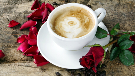 Cappuccino coffee and roses. A cup of latte, cappuccino or espresso coffee with milk put on a wood table with dark roasting coffee beans. Drawing the foam milk on top.