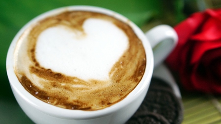 Cappuccino coffee and chocolate cookies. A cup of latte, cappuccino or espresso coffee with milk put on a wood table with dark roasting coffee beans and cookies. Drawing the foam milk on top.