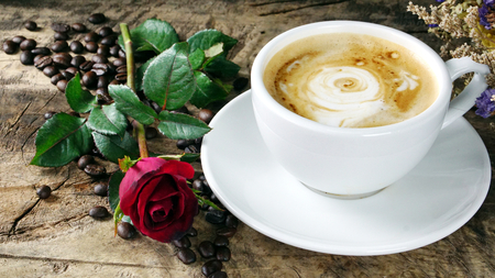 Cappuccino coffee. A cup of latte, cappuccino or espresso coffee with milk put on a wood table with dark roasting coffee beans and cookies. Drawing the foam milk on top.