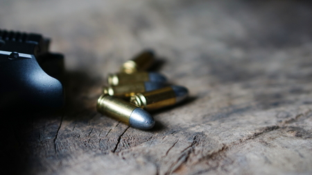 muzzle loading: Bullets and a firearm on the wood. Bullets are a projectile expelled from the barrel of a firearm. Stock Photo