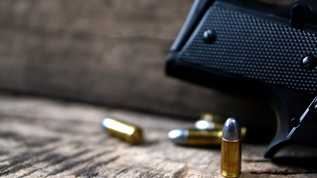 supersonic: Bullets and a firearm on the wood. Bullets are a projectile expelled from the barrel of a firearm. Stock Photo
