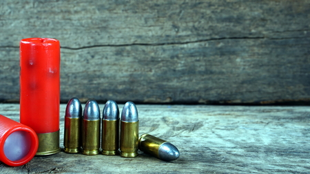 Bullets and a firearm on the wood. Bullets are a projectile expelled from the barrel of a firearm. Stock Photo