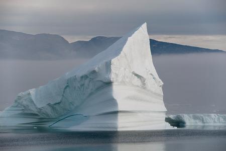 icefjord: Icebergs in mist of polar regions, Greenland Stock Photo