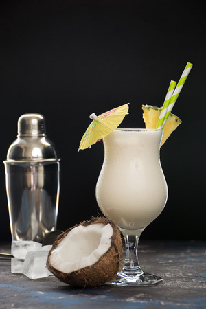 Cocktail pina colada, alcoholic beverage with straws, slice of pineapple and little cocktail umbrella
