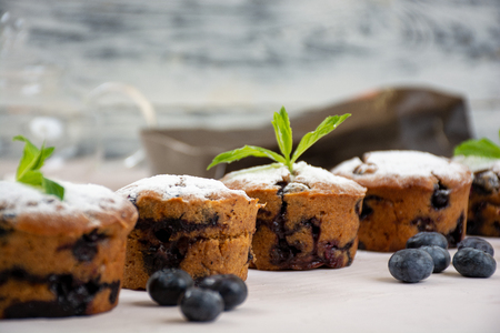 Vegan blueberry muffins with powdered sugar, mint leaves and fresh bluberries 免版税图像