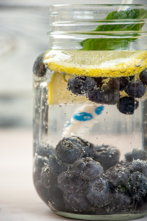 Refreshment drinks, water with frozen and fresh berries, lemons, limes and mint leaves
