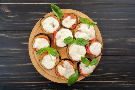 Mini eggplant pizza with mozzarella cheese, tomatoes and basil Imagens - 121134795