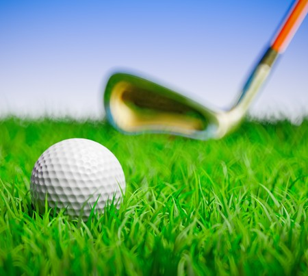 3D render of a golf ball in grass field with out of focus club to the back