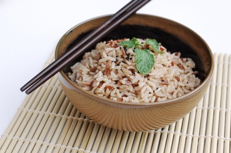 Mixed rice in ceramic bowl with chopsticks on white background