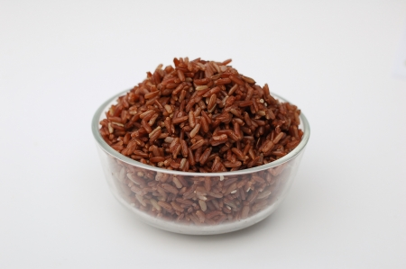 Cooked red rice in glass bowl on white background