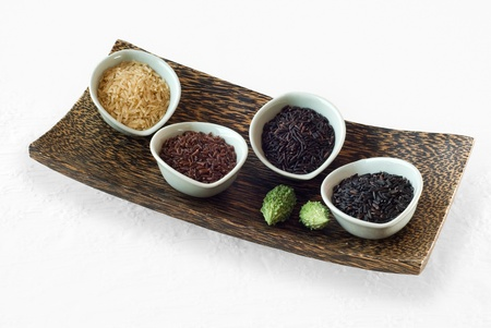 4 bowls of raw rice; brown, red, black, and black sweet rice in rectangle wooden tray