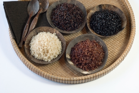 4 bowls of raw rice; brown, red, black, and black sweet rice in round rattan tray Stock Photo