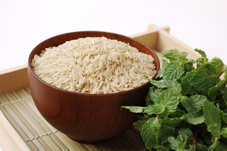 Raw brown rice in wooden bowl on white background photo