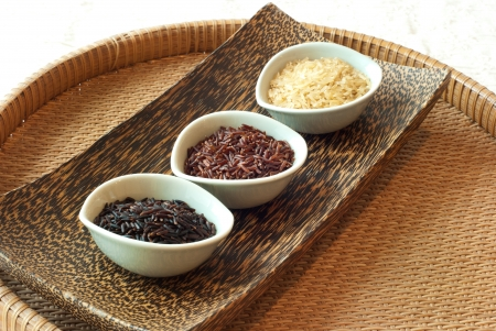 3 bowls of raw rice; brown, red, black rice Stock Photo