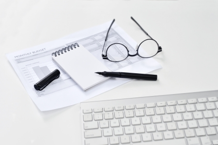 Balance sheet, eye glasses, blank notepad, and pen on the table