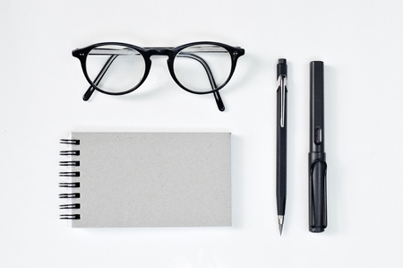 Eye glasses, blank notepad, and mechanical pencil on the table