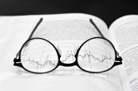 Stock market charts and eyeglasses