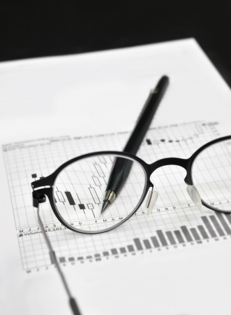 Stock market charts, eyeglasses, and machanical pencil