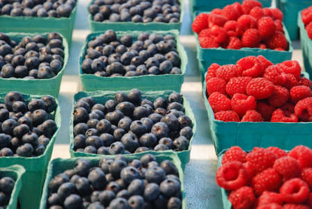 Blueberries and raspberries in box containers at a farmers market Stock Photo
