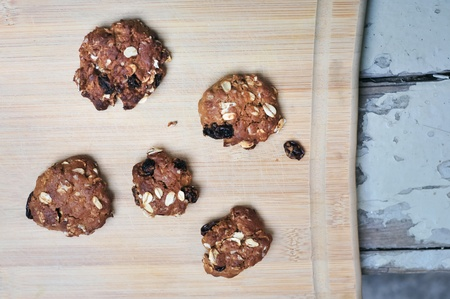 Fresh baked homemade oatmeal raisin cookies on woodem board  brown colour from sugar  photo