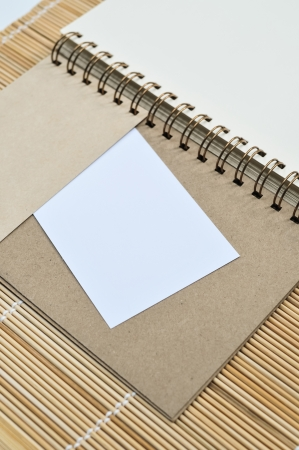 Blank notepad with a piece of paper on bamboo mat background