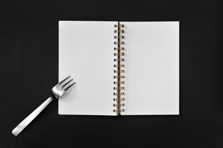 Blank notepad with fork on black - concept   planning and eating