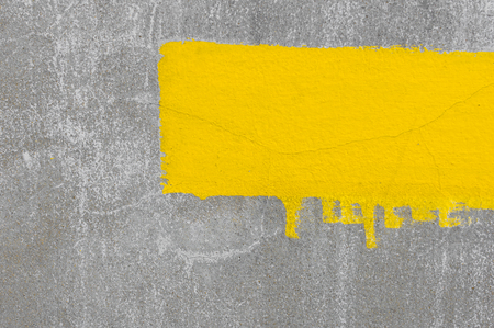 Grey cement wall background with yellow paint photo