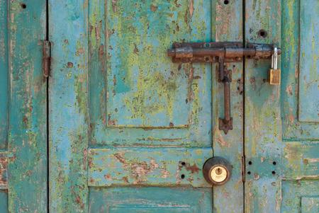 Old Brass Padlock on Wooden Green Door photo
