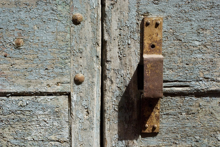 A rusty white door with a doorhandle. closeup. photo