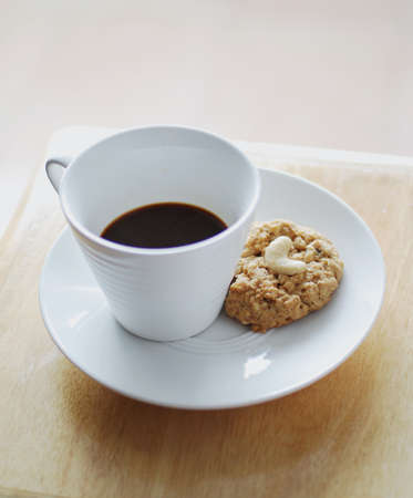 Coffee cup and cookies on wooden table background photo