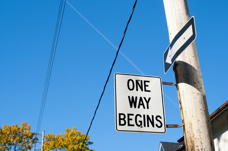 One way begins street sign and arrow sign Stock Photo