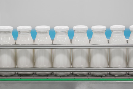factory machine: Conveyor with glass bottles filled with milk products Stock Photo